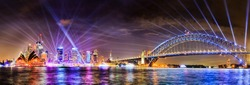 WIde panorama of Sydney city CBD landmarks and high-rise office buildings on waterfront of Harbour with the Sydney harbour bridge at Vivid Sydney light show illumination.