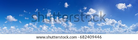 Wide panorama of the blue sunny sky with white cumulus clouds