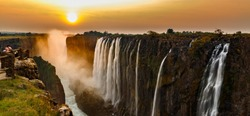 Wide panorama of victoria falls at sunset with orange sun in the sky and tourist in viewpoint