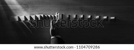 Wide panorama top view of businessman stopping falling blocks on table, monochrome image.