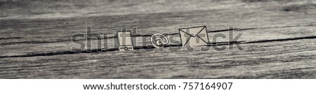 Wide panorama view of at sign, mail and mobile phone icons stuck in between a crack in the wooden surface, toned retro effect. #757164907