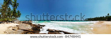 Wide panoramic photo of a beautiful tropical beach with boulders and palms. Tangalla, Sri Lanka