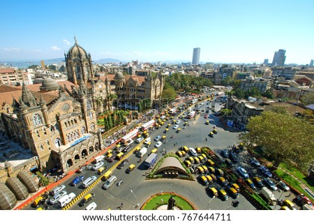 Wide panoramic sweep and bird's eyeview of Chatrapati Shivaji Terminus and surrounding heritage precinct in South Mumbai with statue of Dadabhai Naoroji in the foreground  Stock fotó ©
