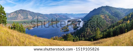 Photo of  Wide panoramic view, autumn. The Yenisei River flows through a picturesque valley. Blue water and islands. South of Western Siberia. Travels in Russia and Asia.
