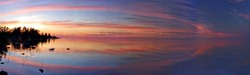 Wide panoramic view of Ladoga Lake with mirror reflection and red clouds, Russia. Incredible colorful red sunset over still surface of water on white nights. Semicircle of line of clouds above lake.