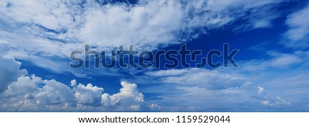 Wide panoramic view of romantic navy blue sky with white grey clouds. High resolution artistic skyline background image. Sky panorama