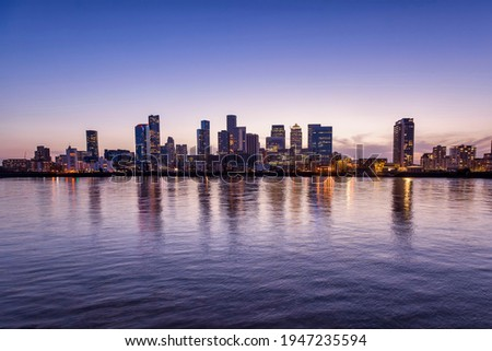 Wide panoramic view over the Thames river to the new skyline of the financial district Canary Wharf in London, United Kingdom, during dusk Stockfoto ©