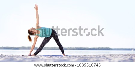 Wide picture of a woman practicing triangle yoga pose at the sandy river beach