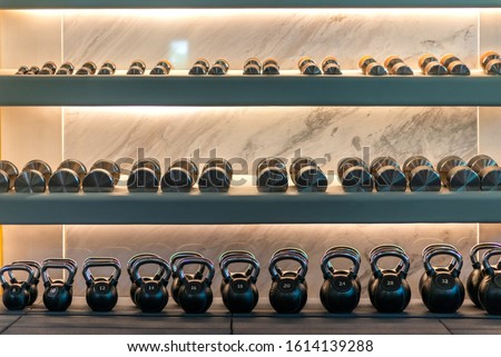 Wide range of choices. Kettlebells weights and dumbbells lying in a row on shelves in stylish workout gym. Marble background. Sport, healthy lifestyle concept. Horizontal shot.