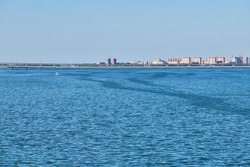 Wide river and bridge over. Little city background. Blue clean water and sunny day. Shipping and navigation available