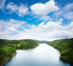 Wide river with green coasts and sky with clouds