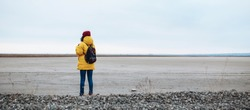 Wide shot backview of a young woman tourist with a backpack walking on sideroad among vast empty winter valley lowland. Female wearing yellow jacket and red hat. Hitch-hiking, travelling concept.