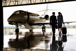 Wide shot of a businesswoman and a businessman walking towards private jet