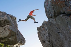 Wide shot of a male rock climber leaping between rocks.