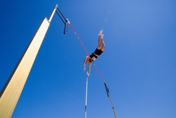 Wide shot of a pole vault athlete going over bar with a clear blue sky and lens flare in the background.