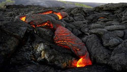 wide shot of a slow lava flow from kiiaeua volcano on the island of hawaii