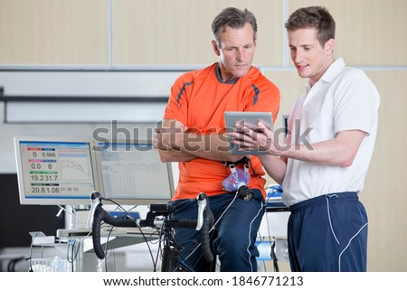 Wide shot of a sports scientist explaining a senior man sitting on an exercise bike some fitness data in a laboratory Сток-фото ©