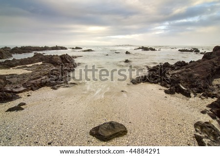 Wide shot of a very rocky beach with stormy clouds overhead. A single round rock in the foreground
