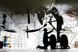 Wide shot of an engineer inspecting the landing gear of a passenger jet at a hangar.