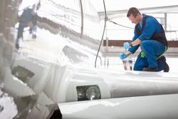 Wide shot of an engineer repairing the wing of a passenger jet at a hangar.