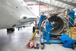 Wide shot of engineers assembling an engine of a passenger jet at a hangar.