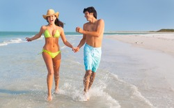wide shot of Latin young Man and Woman running through surf and holding hands on Florida Beach