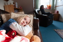 Wide shot of sad and lonely pretty young blonde girl with an adult out of focus in the background