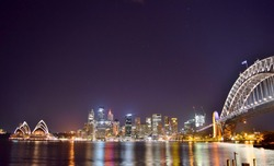 Wide Shot of Sydney Skyline, Opera House, Harbor, and Harbor Bridge under a Starry Night (low angle) - Sydney, Australia