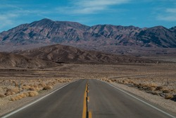 Wide shot of the  road in the desert, with a mountain straight ahead