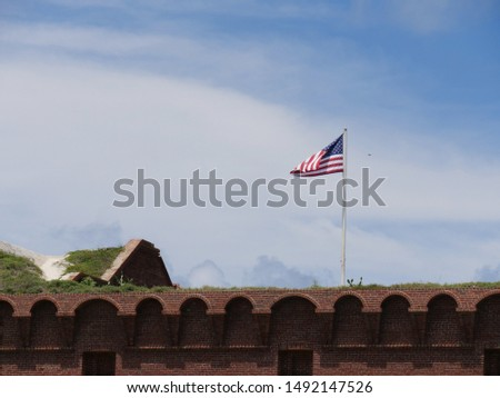Wide shot of the top portion of Fort Jefferson with a US flag flying from a pole at the Dry Tortugas National Park, Florida. #1492147526