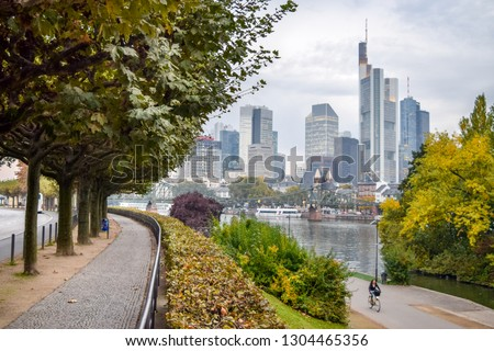 Wide Shot of Walking and Bike Paths in Urban Riverside Park, with the Skyline of Downtown Frankfurt in the Background (Fall / Autumn) - Frankfurt, Germany