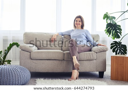 Wide shot of woman in fashionable clothes sitting on sofa in bright living room