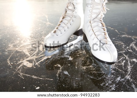Wide skates on ice with sun reflected in behind