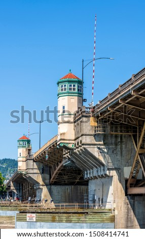 Wide truss Burnside drawbridge over the Willamette River in down town of Portland Oregon with towers on concrete supports with hoisting mechanisms for raising the central part of the bridge
