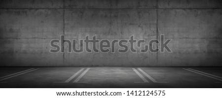 Wide Urban Concrete Garage Dark Wall and Car Parking Floor with Spot Light