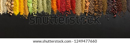 Wide variety spices and herbs on background of black table, with empty space for text or label. #1249477660