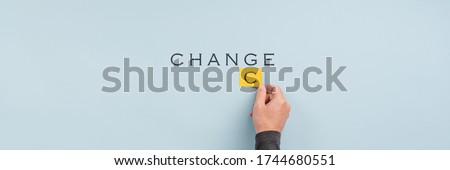 Wide view image of male hand changing the word Change into Chance in a conceptual image. Over light blue background with copy space. Stock fotó ©