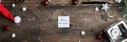 Wide view image of white post it paper with a Merry christmas sign placed on rustic wooden desk in the middle of holiday ornaments and setting.
