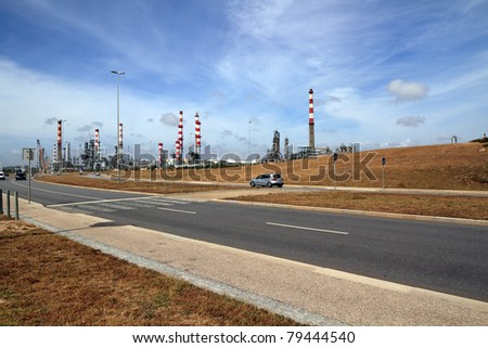 Wide view of a big oil refinery and powerplant near a road