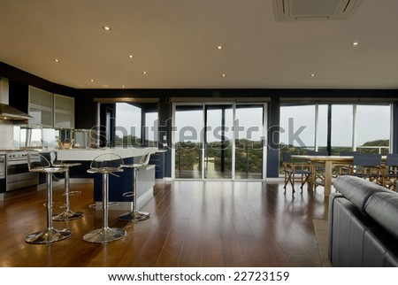 Wide view of a deluxe living area. Kitchen, dining with scenic view from the windows.