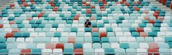 WIDE view of a lonely fan spectator attending a sports event on an empty stadium. Isolation, events during coronavirus pandemic concept