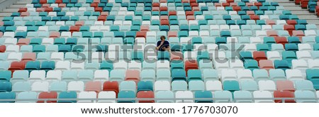 WIDE view of a lonely fan spectator attending a sports event on an empty stadium. Isolation, events during coronavirus pandemic concept Stock photo ©