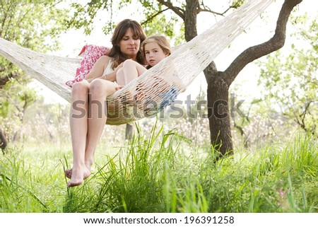 Wide view of a mother and daughter relaxing together being thoughtful sitting in a hammock, hugging and lounging during a sunny summer day in a holiday home garden with grass and trees, lifestyle.