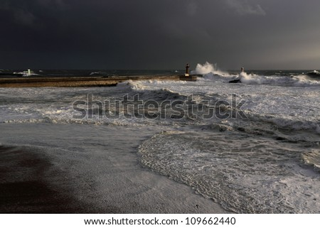 Wide view of a stormy sunset at the harbor of the mouth of the river Douro, in Porto, Portugal, with big waves against old lighthouse, new pier, beacons and seaside