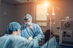 Wide view of a team of four surgeons operating on a patient in a dark OR at a hospital
