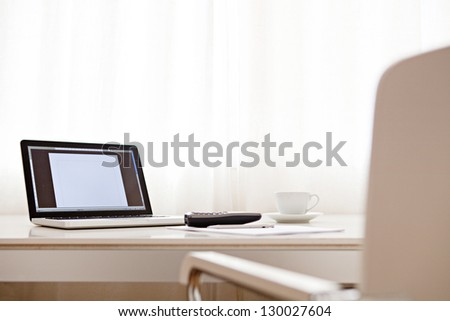 Wide view of a work desk interior with a laptop computer, a cup of coffee and white curtains on a sunny day.