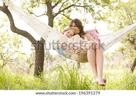 Wide view of a young mother and daughter relaxing together and smiling sitting in a hammock, hugging and lounging during a sunny summer day in a holiday home garden with grass and trees, lifestyle.