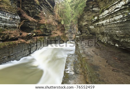 Wide view of Enfield Creek churns through a gorge and under a stone arch at Robert Treman State Park near Ithaca, NY