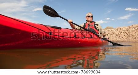 Wide View of Man Paddling Kayak