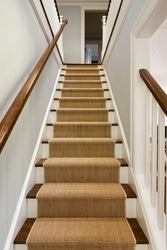 Wide View of wooden staircase with carpet runner and white molding.
